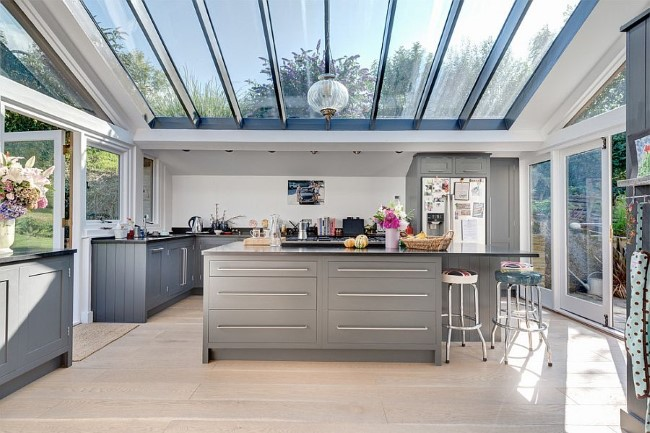 Стильная кухня в сером цвете со стеклянным потолком и стенами.