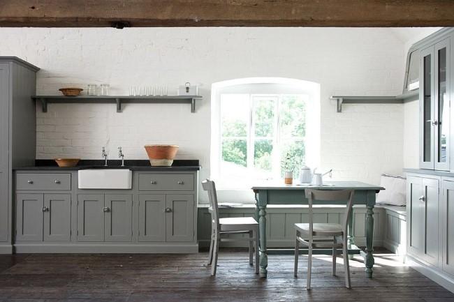 Деревенская серая кухня с деревянными балками и белыми стенами.
