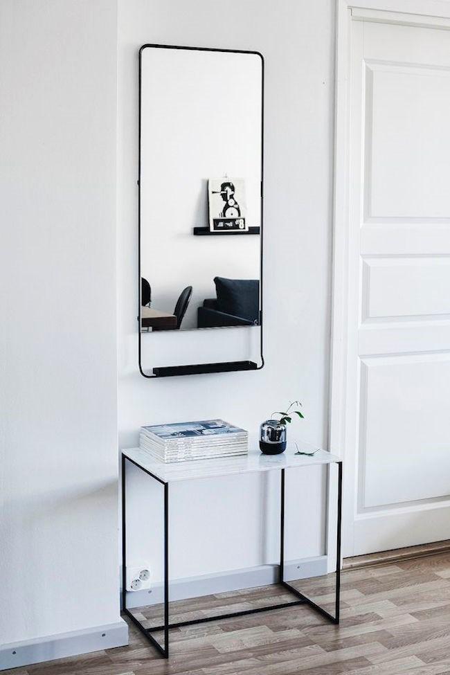 Скандинавская прихожая с прямоугольным узким зеркалом и столиком в минималистическом стиле.