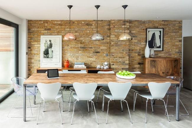 Блестящие хромированные люстры в современной столовой с каменной стеной.