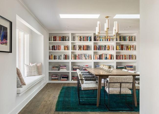 Вместительные полки для книг на стену и уютная зона чтения в интерьере столовой.