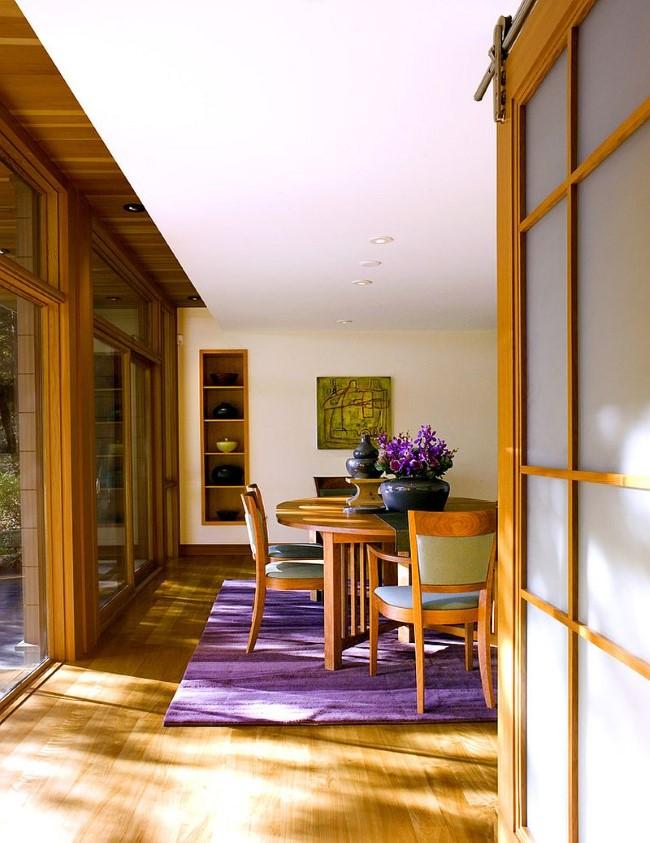 Лавандовое ковровое покрытие и живые цветы в интерьере современной гостиной-столовой.