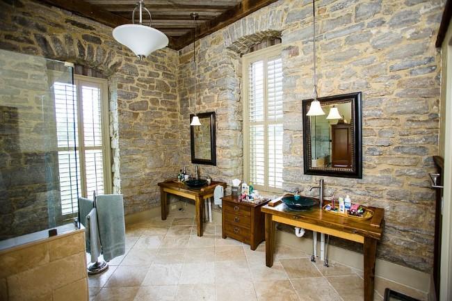 Полированная деревянная мебелью и зеркала в черных рамах в интерьере деревенской ванной.