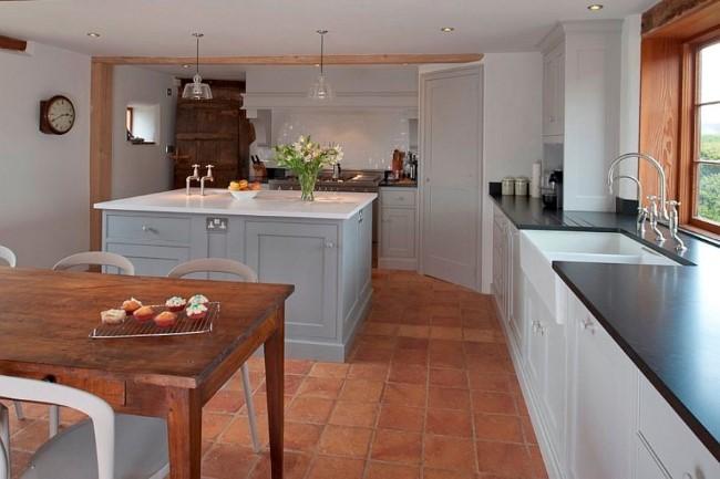 Светло-коричневая терракотовая плитка на полу английской кухни-столовой.