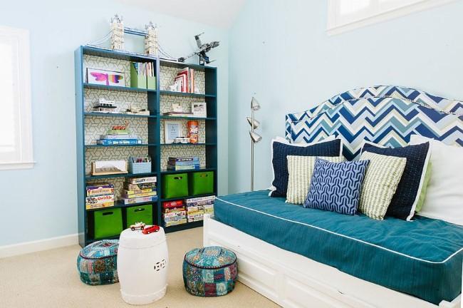 Сине-белый раскладной диван в интерьере небольшой игровой-гостевой комнаты.