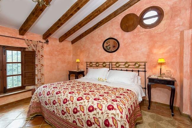 Матовая терракотовая плитка на полу уютной мансардной спальни в деревенском стиле.