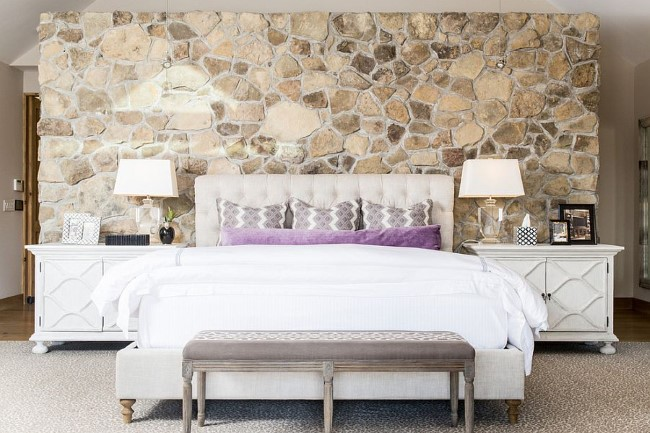 Современная спальня со шлифованной каменной стеной.