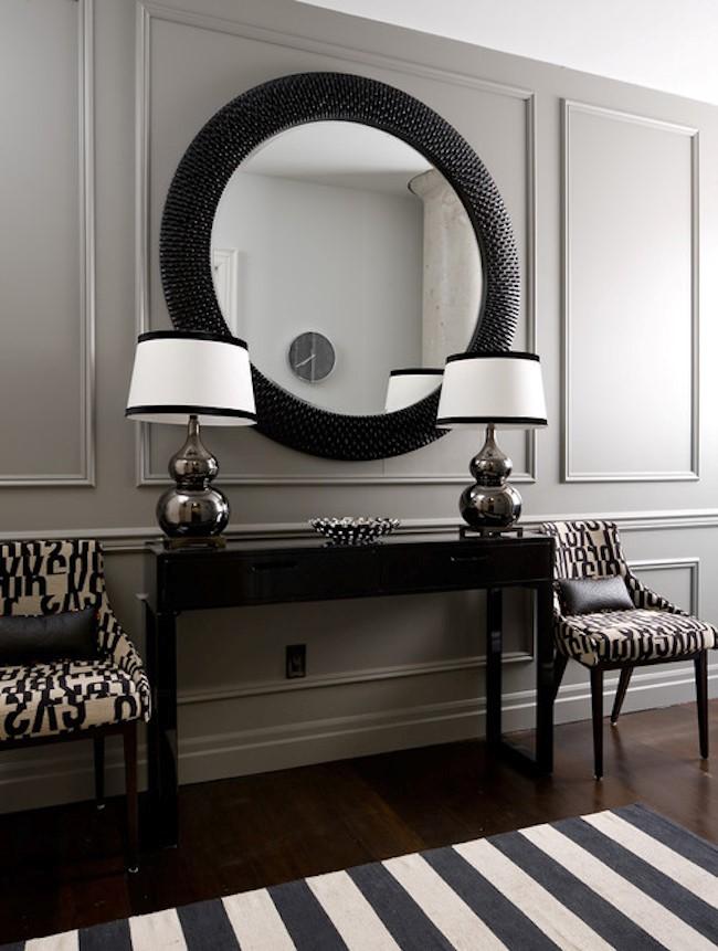 Элегантная классическая прихожая частного дома с круглым стильным зеркалом в массивной черной раме и глянцевым деревянным комодом.