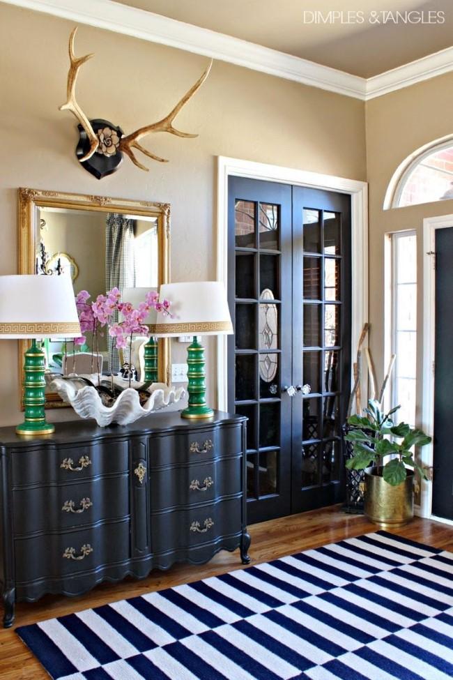 Просторная прихожая в эклектическом стиле с позолоченным зеркалом, рогами и классическим комодом.