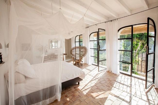 Просторная спальня в средиземноморском стиле с терракотовой плиткой и мебелью из ротанга.