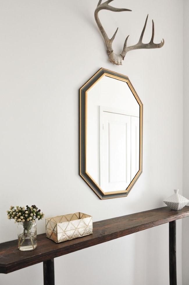 Минималистическое зеркало с оленьими рогами и винтажные аксессуары в интерьере прихожей.