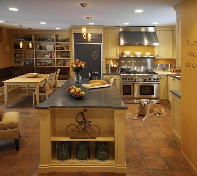 Уютная кухня-столовая в теплых тонах с терракотовой напольной плиткой.