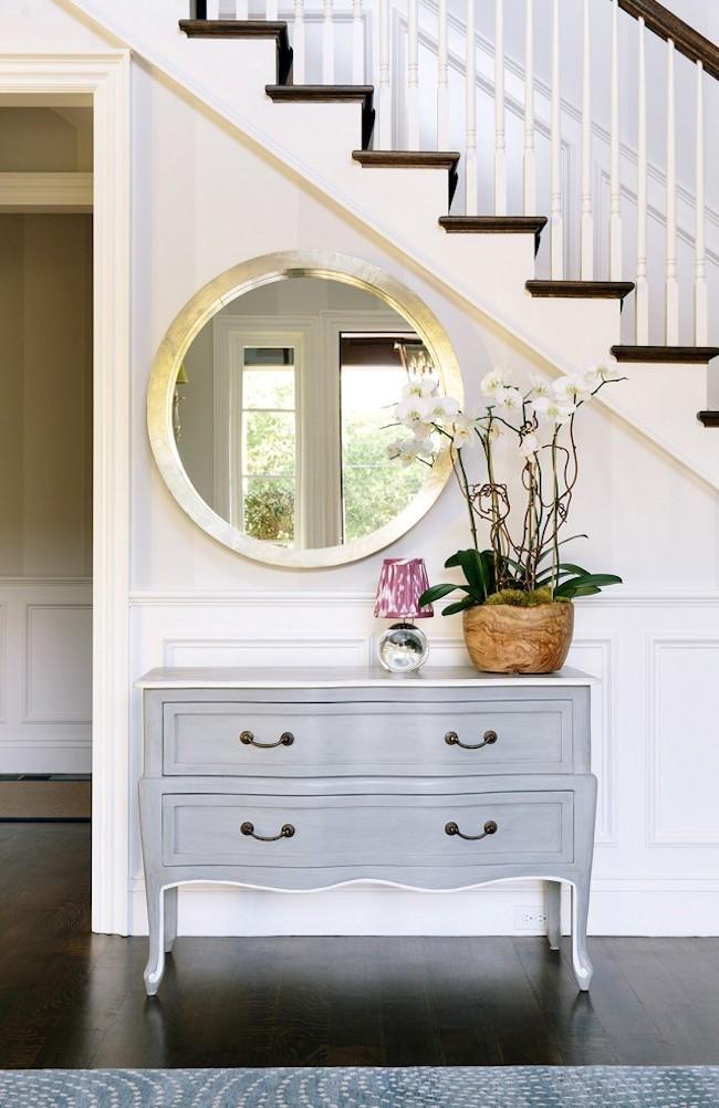 Элегантная прихожая частного дома с круглым позолоченным зеркалом и комодом.