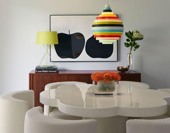 Зеленая настольная лампа и разноцветный потолочный светильник в интерьере маленькой столовой.