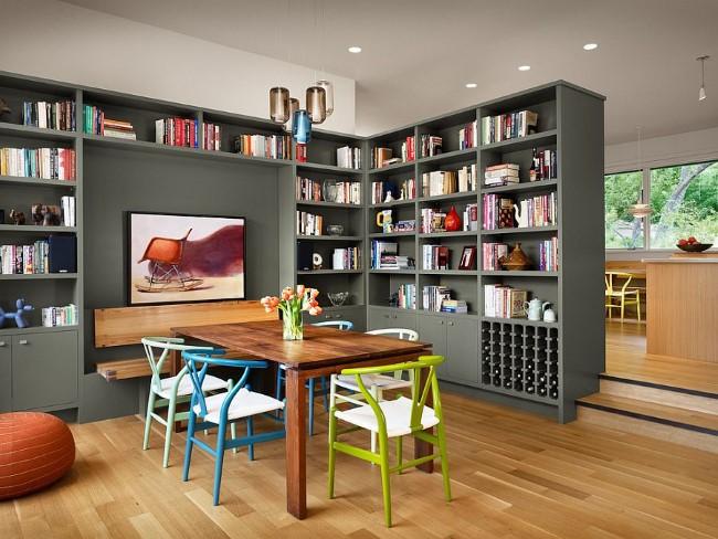 Современная яркая столовая с вместительными книжными шкафами и стеллажами.