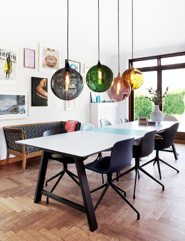 Яркая столовая в деревенском стиле с индустриальной люстрой и разноцветными аксессуарами.