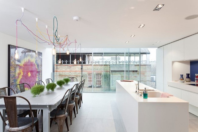 Минималистические лампы Эдисона с разноцветной проводкой и встроенные светильники в кухне-столовой.