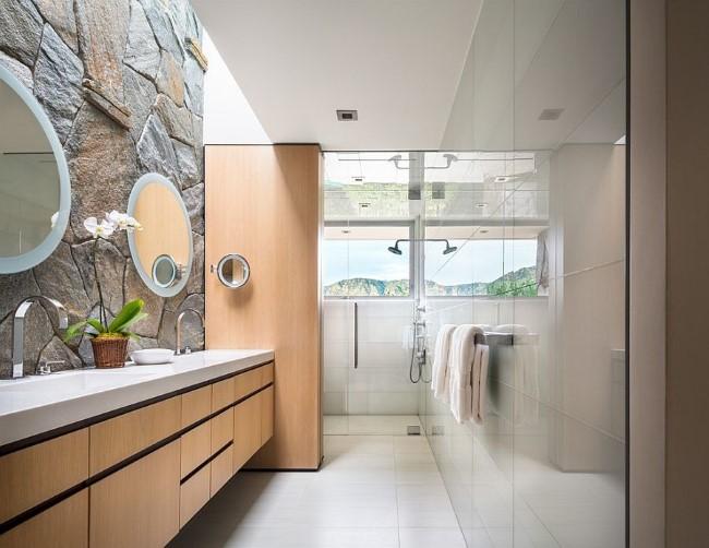 Современная ванная комната со стенами из глянцевой плитки и грубого камня.