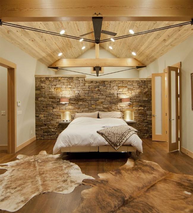 Стильная уютная спальня с каменной стеной и деревянными панелями.