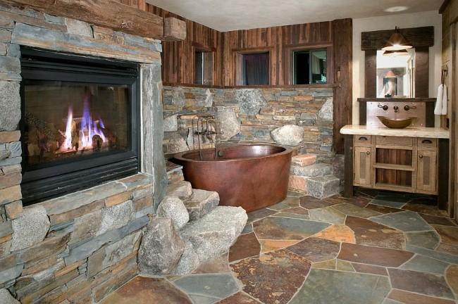 Каменные стены, встроенный камин и мебель из натурального дерева в интерьере стильной ванной.