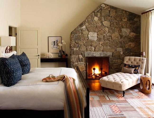 Белые стены и каменный встроенный камине в интерьере современной спальни.