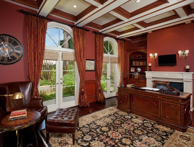 Классическая мебель, винтажные аксессуары и красные обои в интерьере домашнего кабинета.