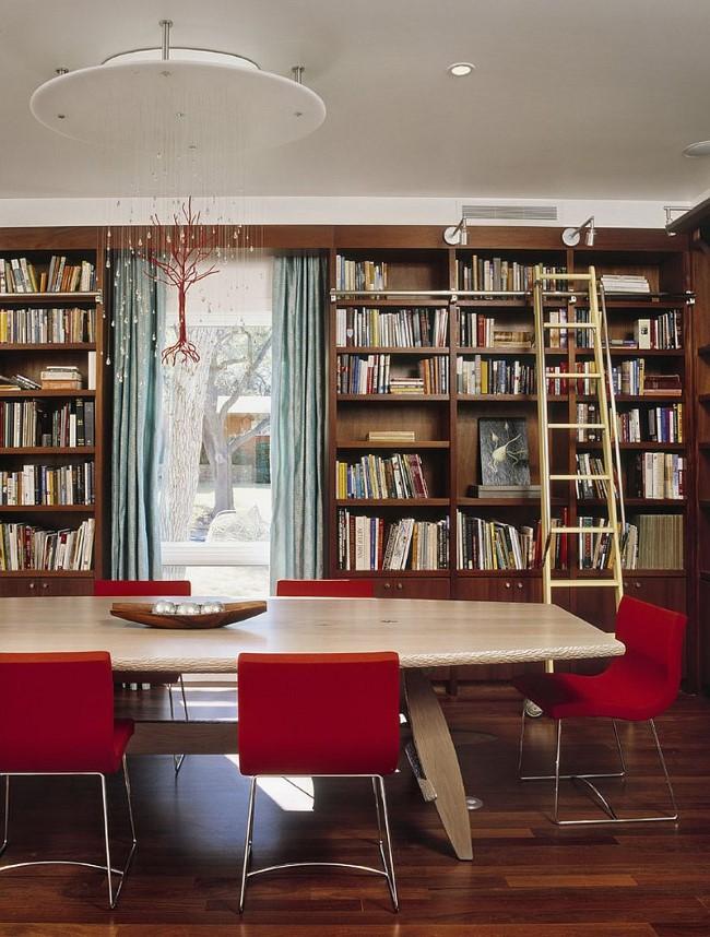 Просторная библиотека-столовая с мягкими креслами для чтения и подвесными светильниками.