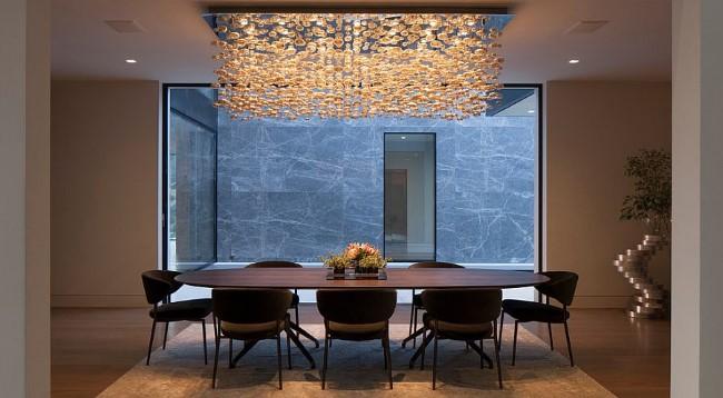 Темно-коричневая деревянная мебель и каскадная люстра в классической столовой.