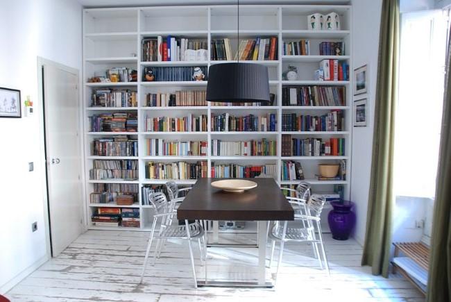 Уютная столовая с книжными полками и зоной чтения у окна.