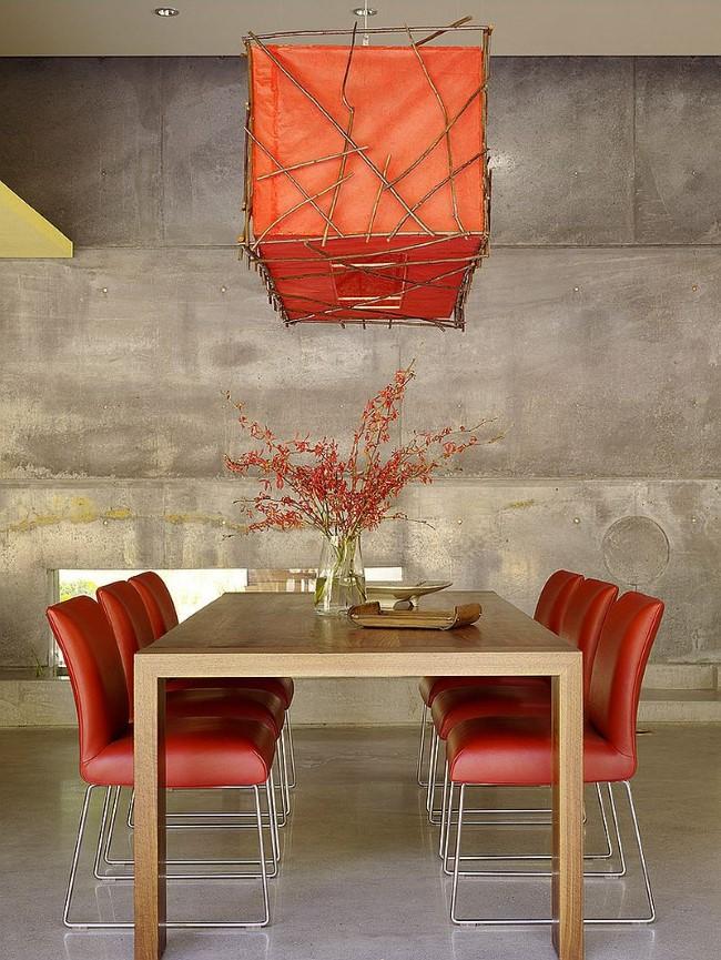 Креативная оранжевая люстра и встроенные потолочные светильники в минималистической столовой.