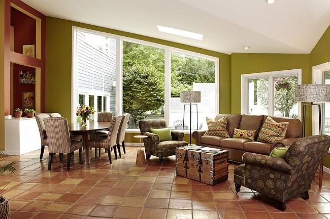 Матовая терракотовая плитка на полу уютной гостиной с зелеными стенами.
