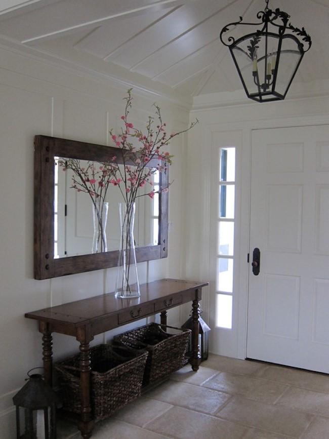 Прямоугольное зеркало в массивной деревянной раме в интерьере стильной светлой прихожей.