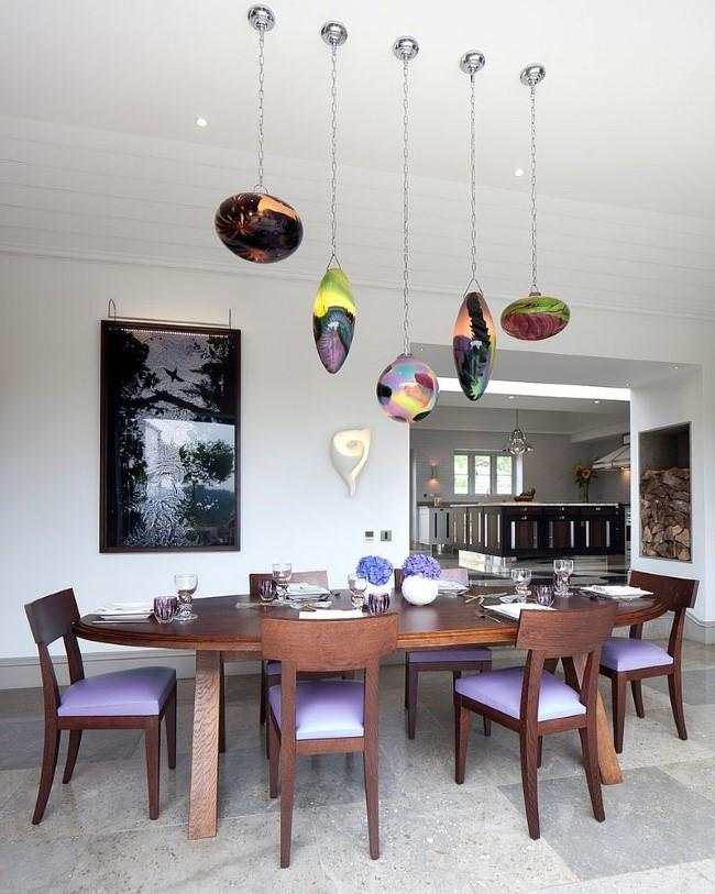 Необычные подвесные светильники из разноцветного стекла в интерьере классической столовой.