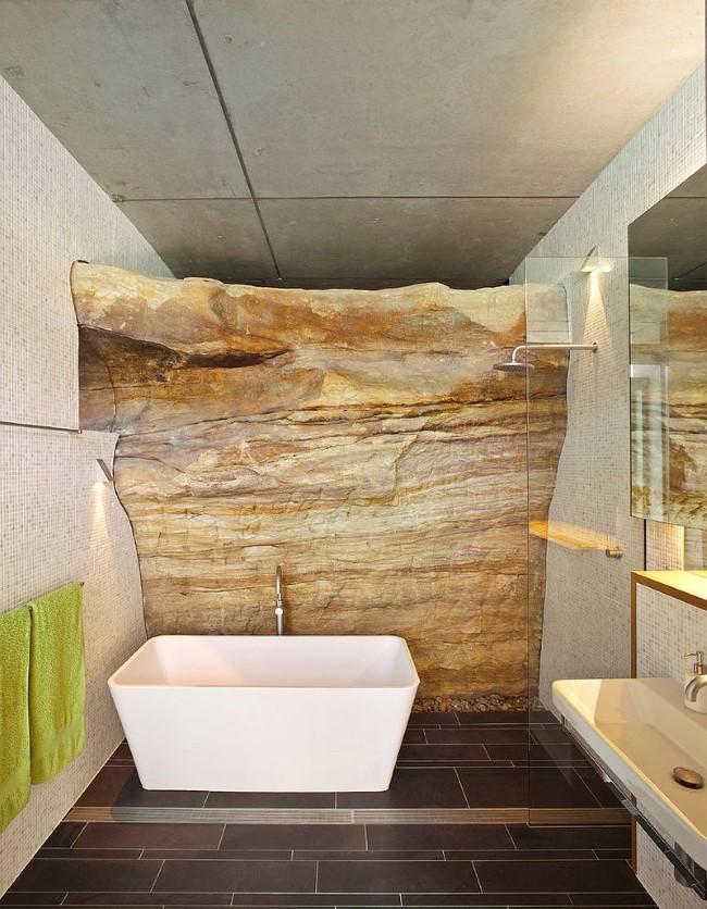 Каменная стена в виде скалы в интерьере современной ванной комнаты.