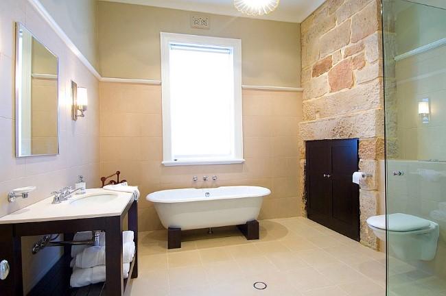 Современная ванная комната с темной деревянной мебелью и персиковыми стенами.