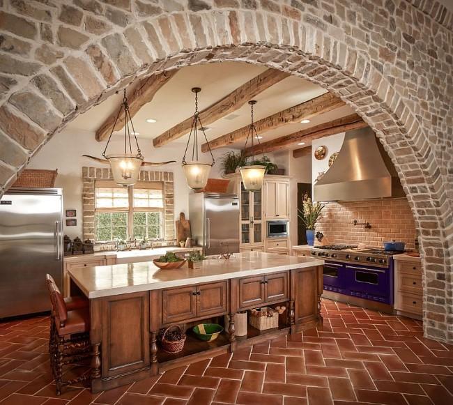 Терракотовая напольная плитка и грубая каменная кладка в интерьере просторной кухни.