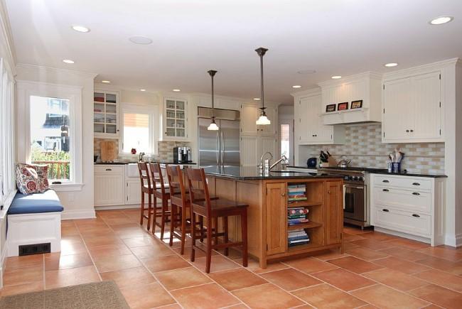 Уютная кухня-столовая в морском стиле со светлой деревянной мебелью и терракотовой плиткой.