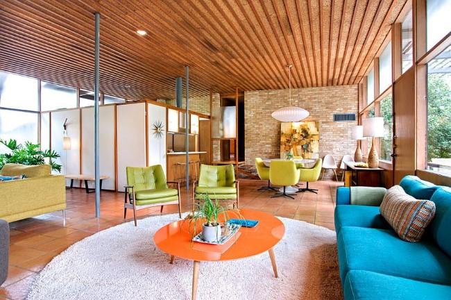 Яркая гостиная-столовая в современном стиле с каменной кладкой и терракотовой плиткой.