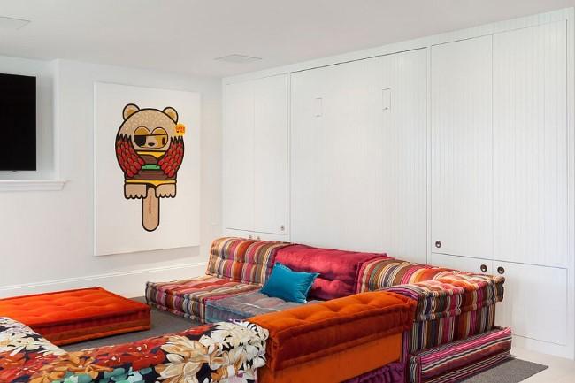 Яркий угловой диван в стильной гостевой-игровой-гостиной комнате.