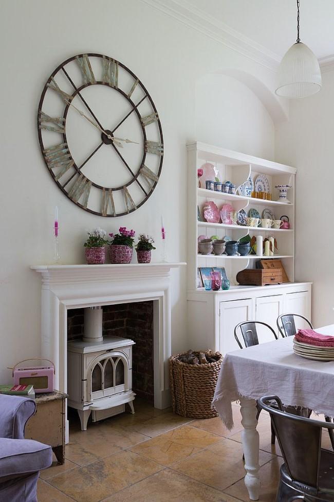 Стильные винтажные часы и ретро-комод в интерьере просторной столовой шебби шик.