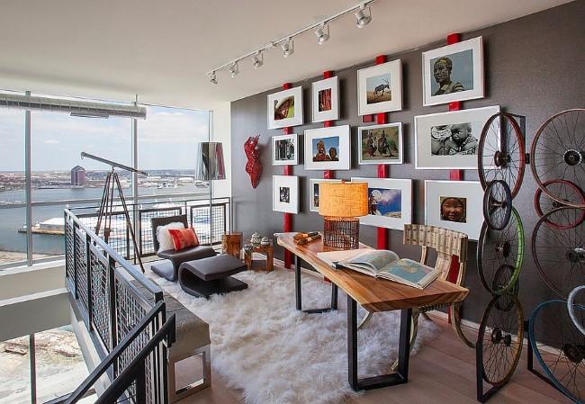 Серый индустриальный кабинет с красными аксессуарами и декоративными элементами.