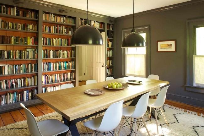 Просторная столовая с вместительными книжными полками и большим обеденным столом.