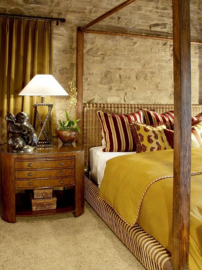 Оформление стены над кроватью в современной спальне каменной грубой кладкой.