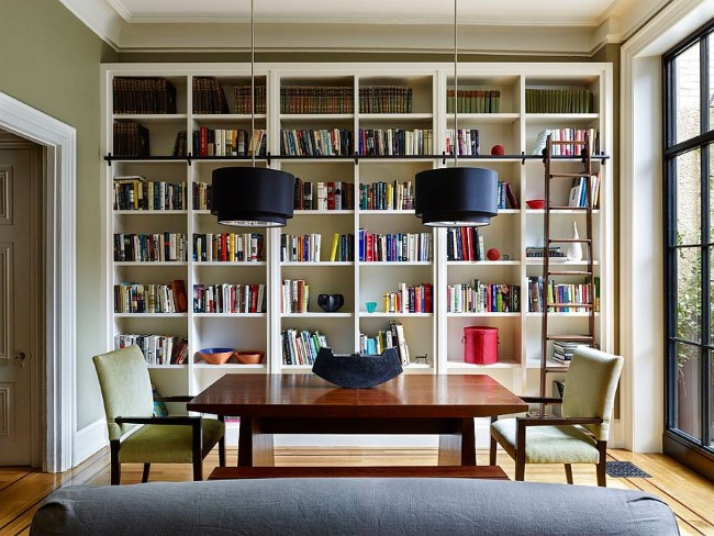 Высокий книжный шкаф с приставной лестницей в интерьере столовой в пастельных тонах.