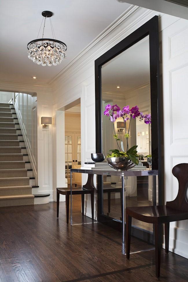Большое настенное зеркало в полный рост со столиком и стульями в интерьере прихожей.
