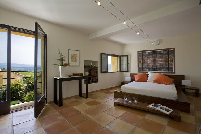 Терракотовая плитка в интерьере просторной современной спальни от Ernesto Santalla.