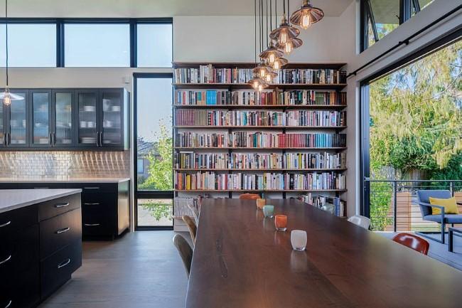 Просторная кухня-столовая с современной мебелью и вместительным книжным шкафом.