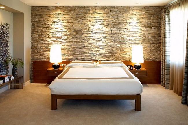 Каменная стена и живые растения в современной просторной спальне.