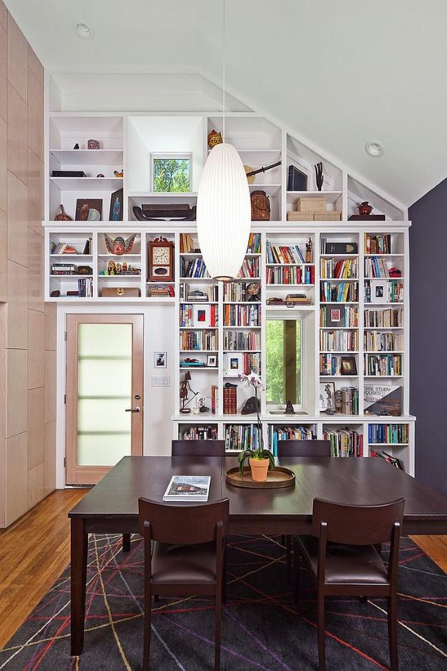 Небольшая уютная столовая с открытыми книжными полками и мебелью из темного дерева.