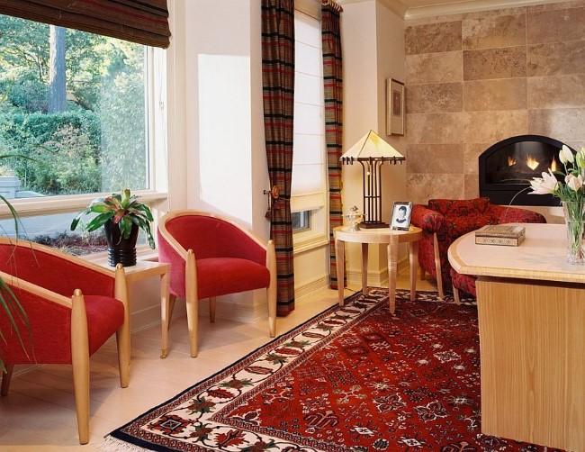 Красная мебель и узорчатое ковровое покрытие в просторном эклектическом кабинете.